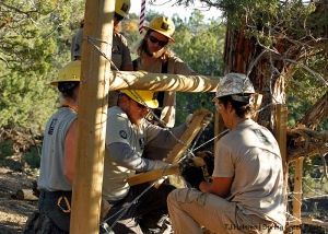 Southwest Conservation Corps crew members Sarah, Zoe, Aaron and Eric watch Jordan as he shows them how to twist staves in crossed wires to pull together an H-brace they installed in Spring Creek Basin's southeastern fence line.