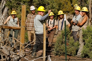 Southwest Conservation Corps' Jordan explains previous fence building by University of Missouri students to SCC crew members along Spring Creek Basin's southeastern fence line. The SCC crew is on site to replace a difficult section of the fence that goes up a steep hill.