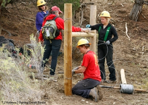 Southwest Conservation Corps co-crew leader Dillon and member Sarah thread wire to complete an H-brace in Spring Creek Basin's southeastern fence line. SJMA's Kathe Hayes offers homemade chocolate chip cookies to Sarah, Aaron and Dillon.