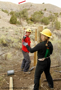 Southwest Conservation Corps co-crew leader Dillon and member Sarah thread wire to complete an H-brace in Spring Creek Basin's southeastern fence line.