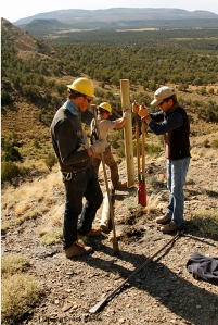 BLM range tech Justin Hunt helps dig a post hole for an H-brace on the steep hill with SCC crew members Toby and Abby on Spring Creek Basin's southeastern boundary.