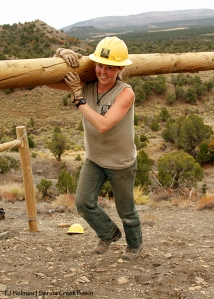 Southwest Conservation Corps co-crew leader Sarah carries a post up the steep hill to build an H-brace in Spring Creek Basin's southeastern fence line. All smiles on Day 4!