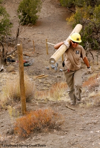 Southwest Conservation Corps crew member Zoe carries a post up the steep hill to use as part of an H-brace along Spring Creek Basin's southeastern fence line.